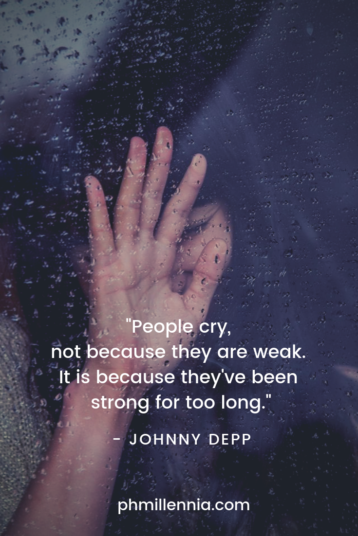 A sad woman crying while her hand is pressed up against the glass pane