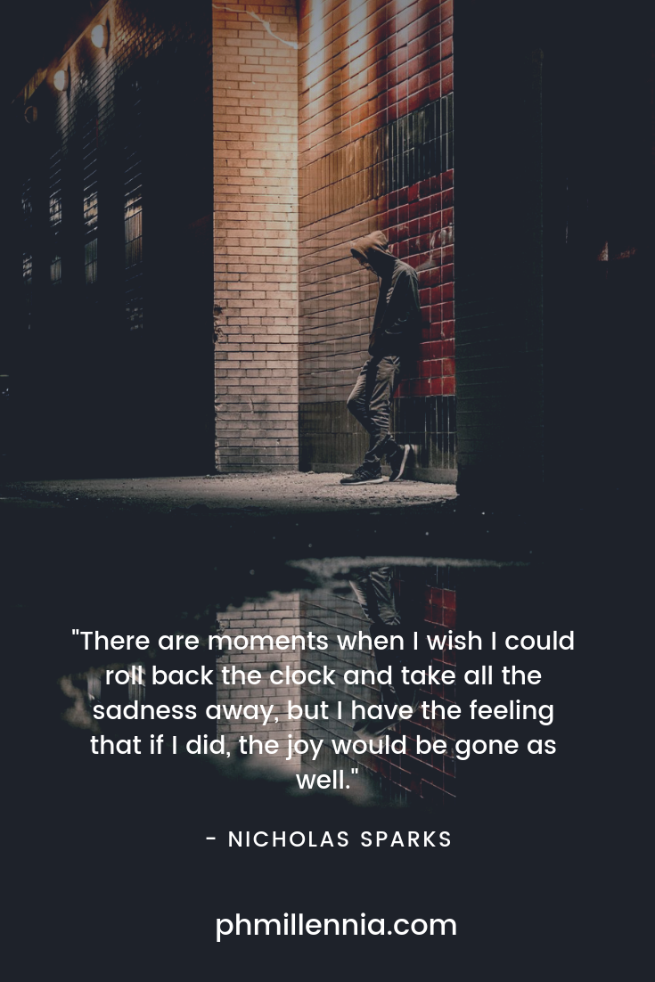 A man in sadness leans against a wall beneath a streetlight