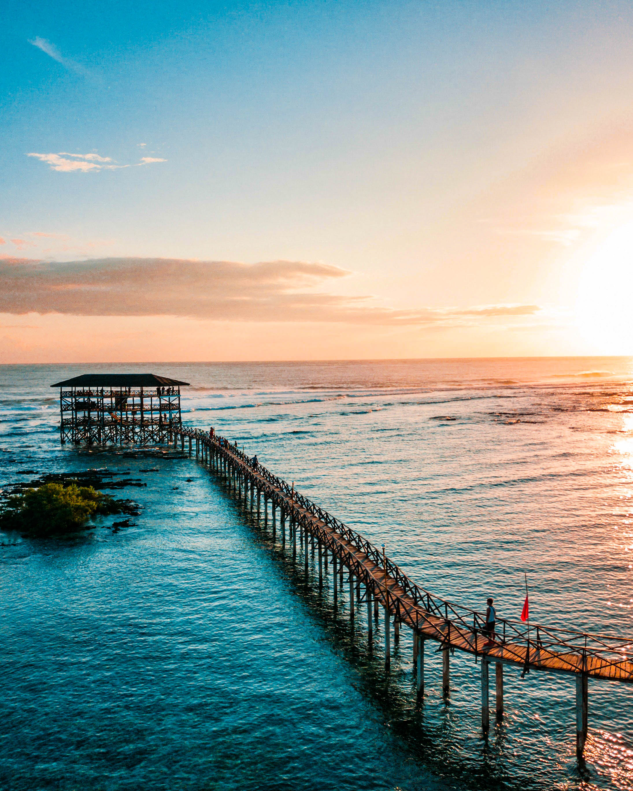 View of a long wooden pier with a three-story viewing deck during sunset in Siargao, Philippines