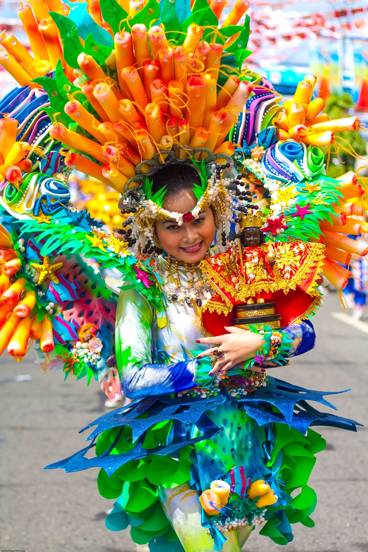 Woman in very colorful costume holding a small statue of the Infant Jesus during a festival parade