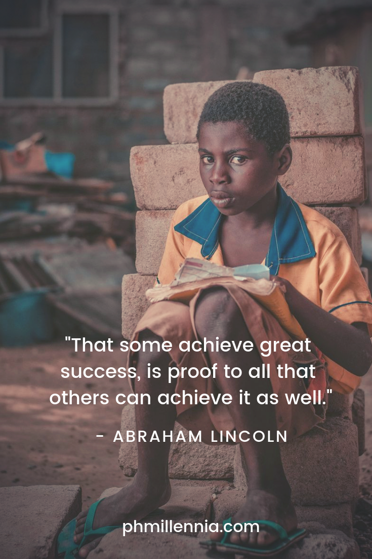 An African boy in overlarge clothes sits upon a rock holding a book in his hand, signifying perseverance in studying no matter the odds.