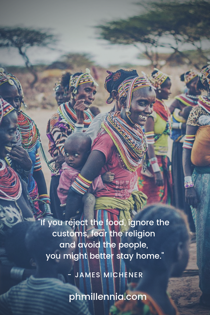 A quote on travel by James Michener on an image of African tribespeople in colorful garb.