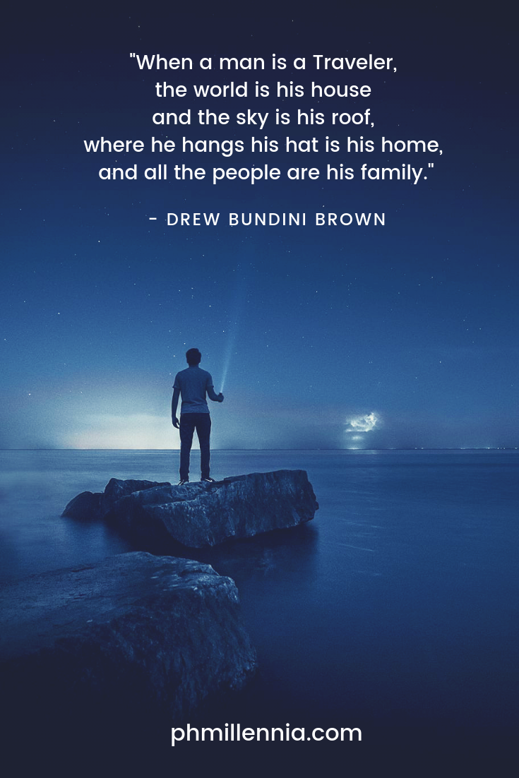 A quote on travel by Drewn Bundini Brown on an image of a man shining a flashlight in the dark