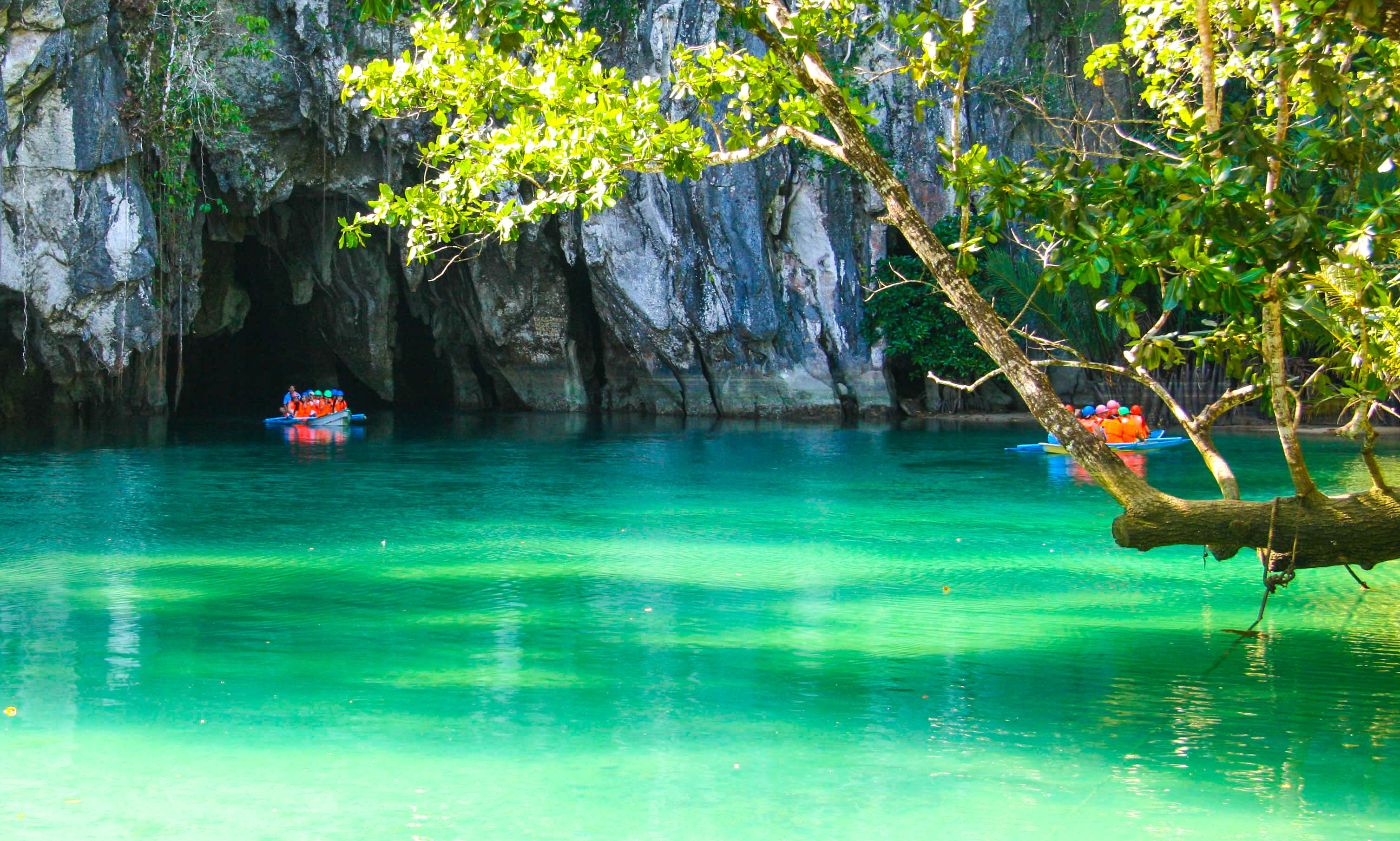 River with turquoise and green waters flows out of a cavern delved on the side of sheer limestone cliffs overhung with verdure in Puerto Princesa Underground River, one of the most amazing places to visit in the Philippines