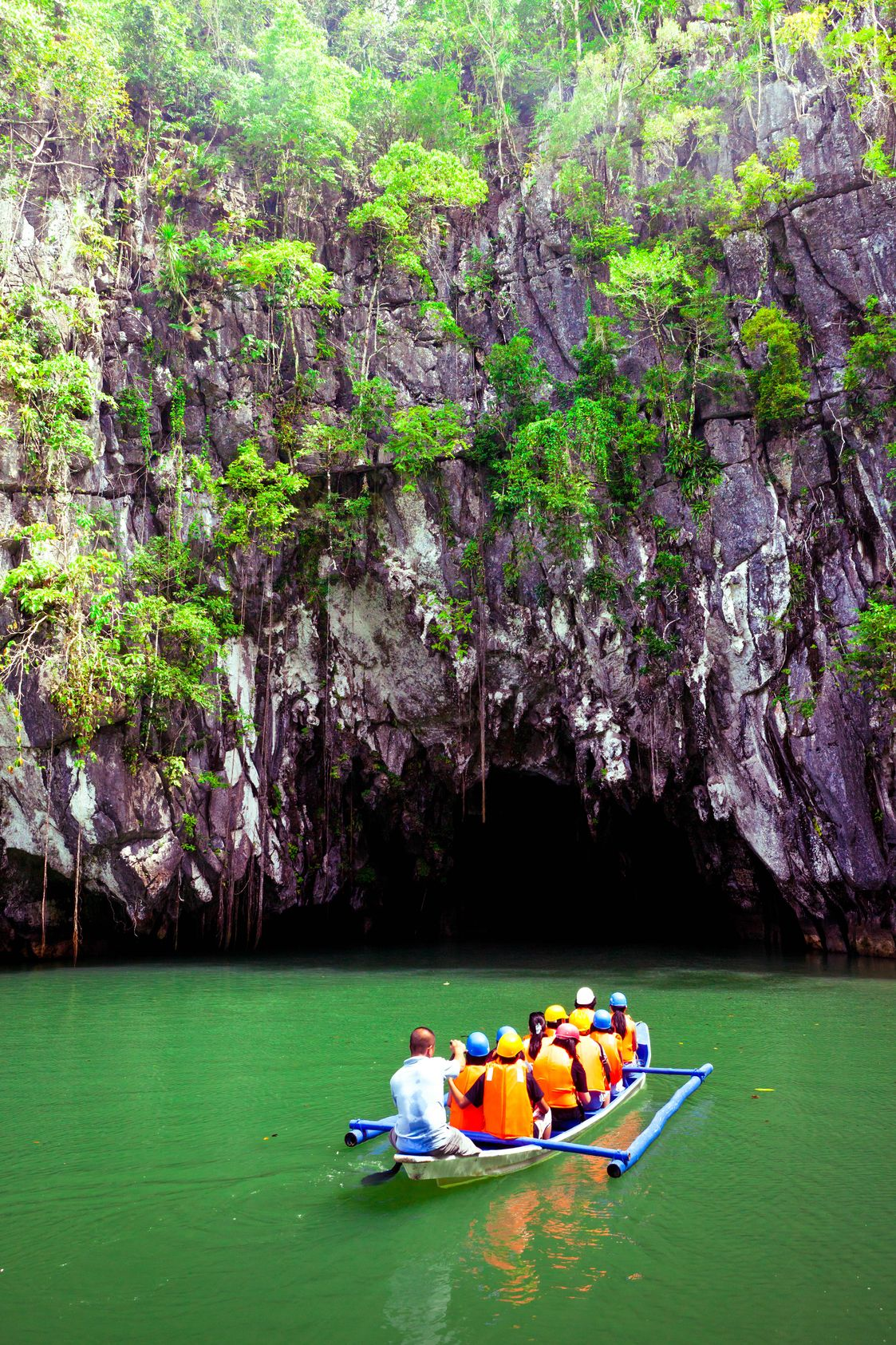 Boat laden with tourists sail along a river towards a gaping cavern beneath limestone cliffs in Puerto Princesa Underground River, Palawan