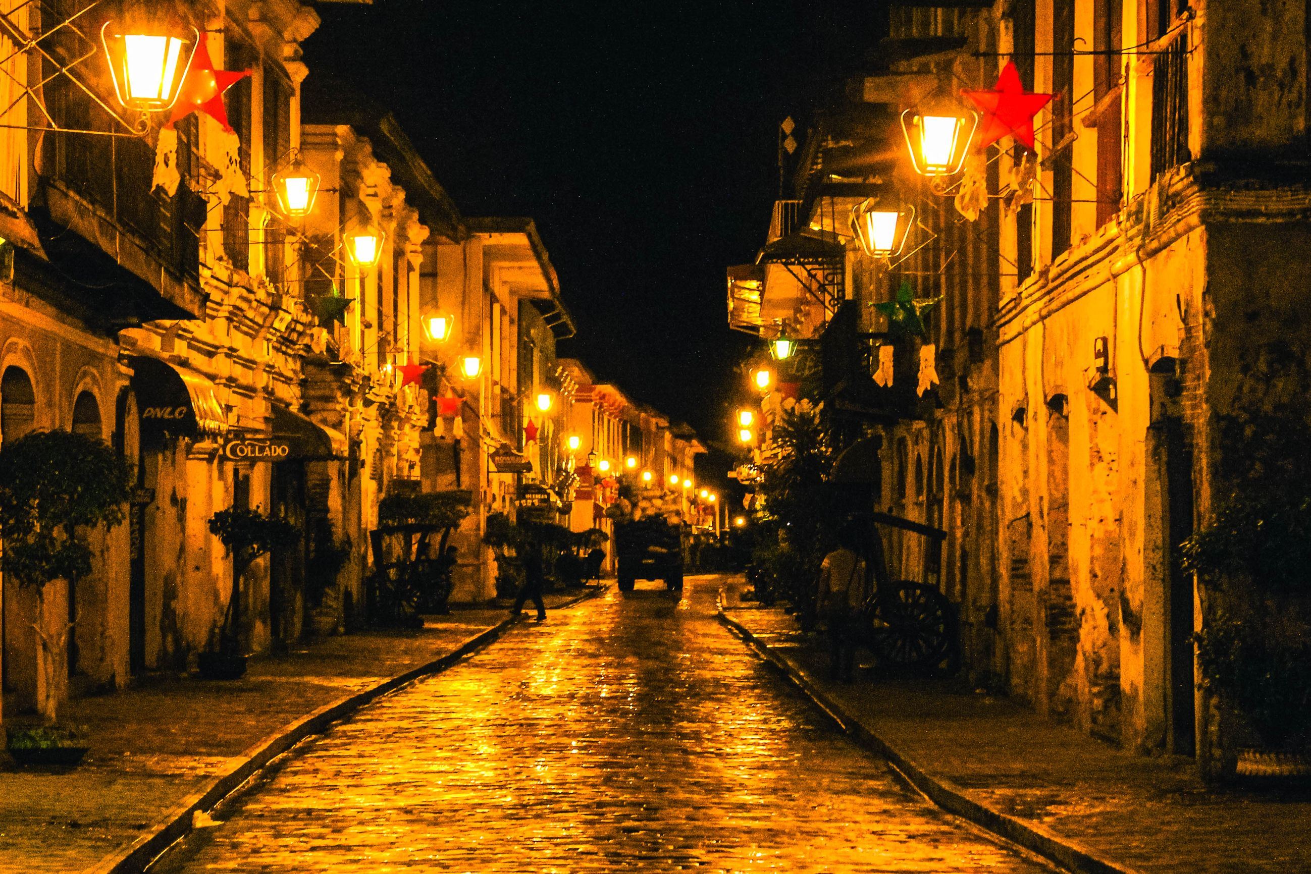 Cobblestone street lined by old Spanish colonial houses lit by yellow and orange lamps at night in Vigan City, Philippines