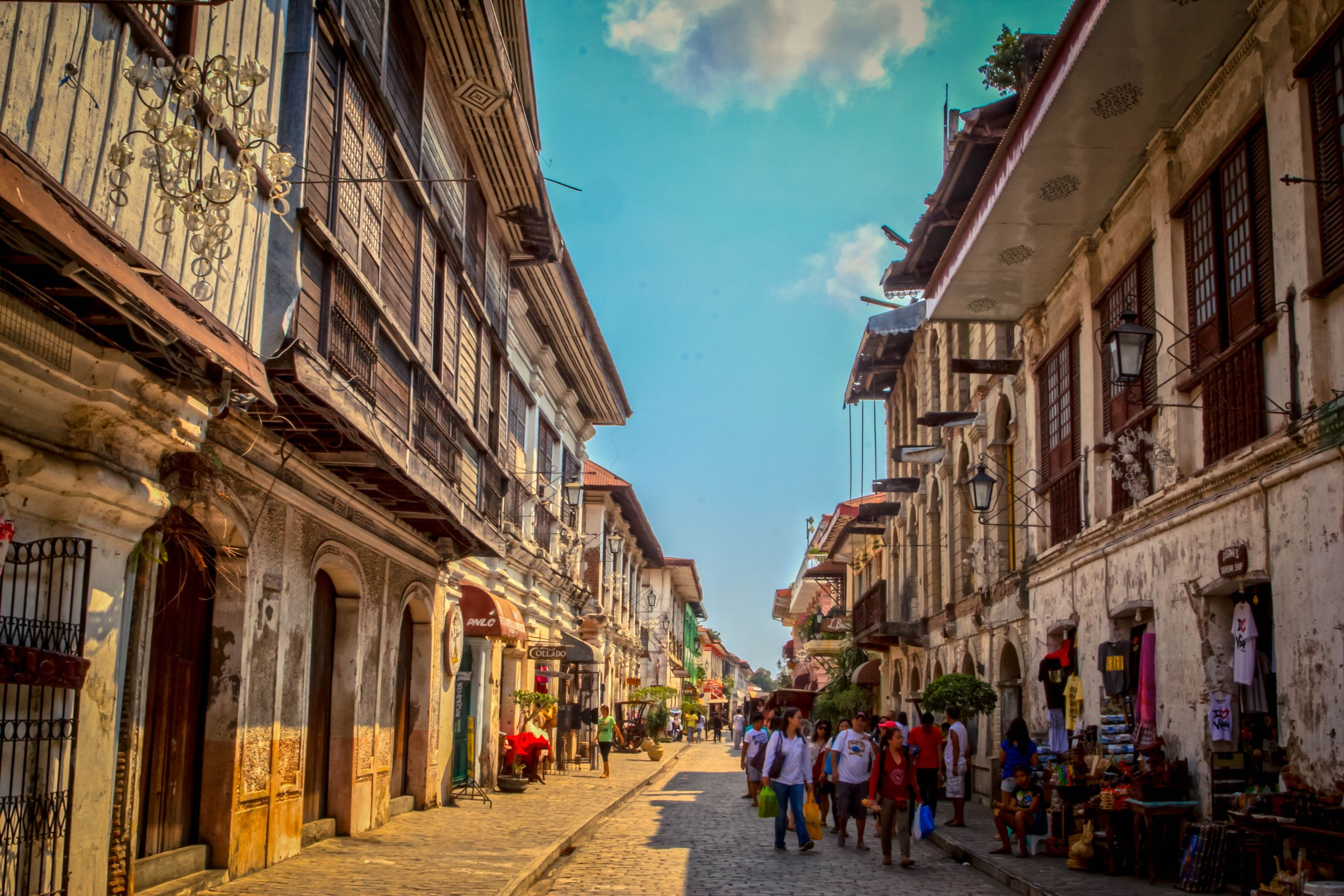 Tourists walk along a cobbled street lined with old Spanish colonial houses in Vigan City, one of the most amazing places to visit in the Philippines
