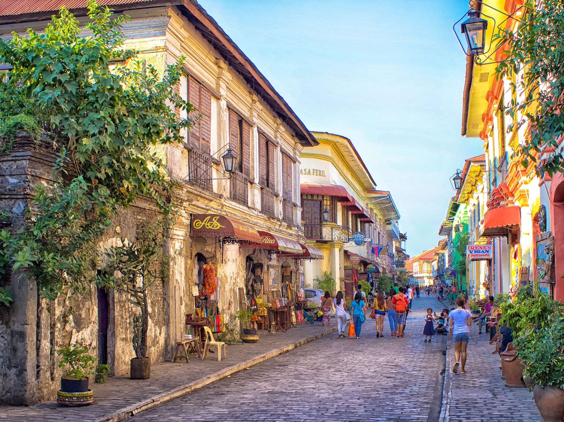 Old Spanish colonial homes and buildings line a cobblestone street where tourists walk along in Vigan, Philippines