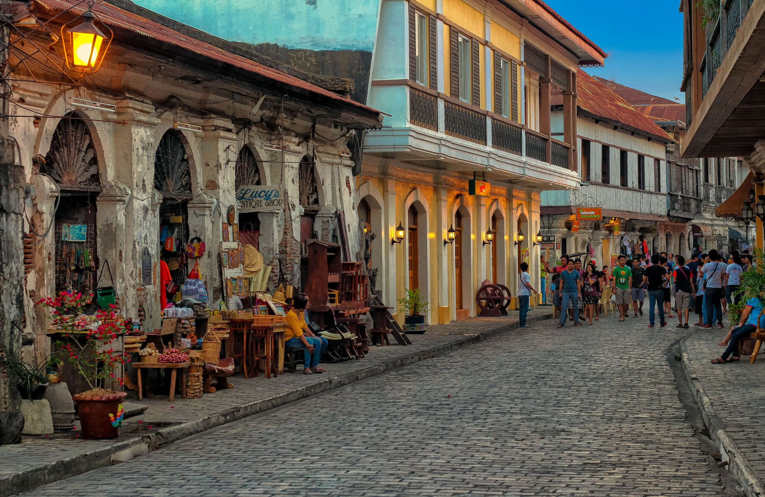Spanish colonial homes and buildings line a cobblestone street where tourists walk along in Vigan, Philippines