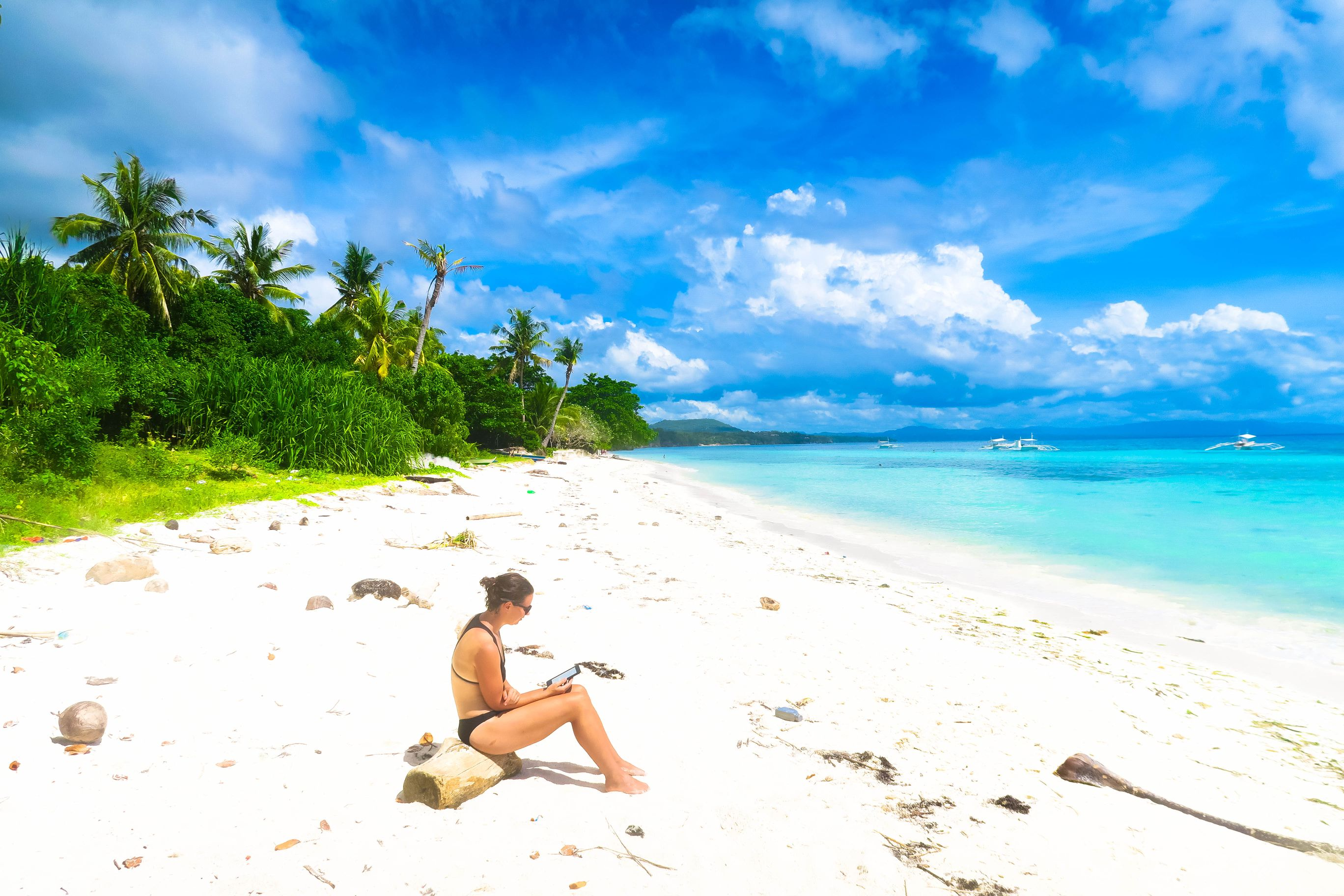 Woman using her phone while sitting on a white sand beach fronting blue and turquoise waters in Panglao, one of the most amazing places to visit in the Philippines