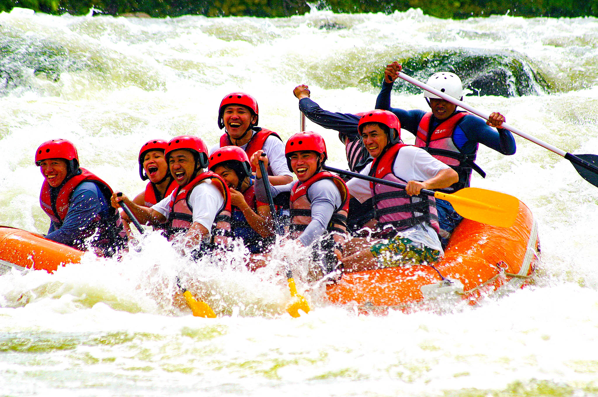 Group of people in a small boat whitewater rafting or kayaking