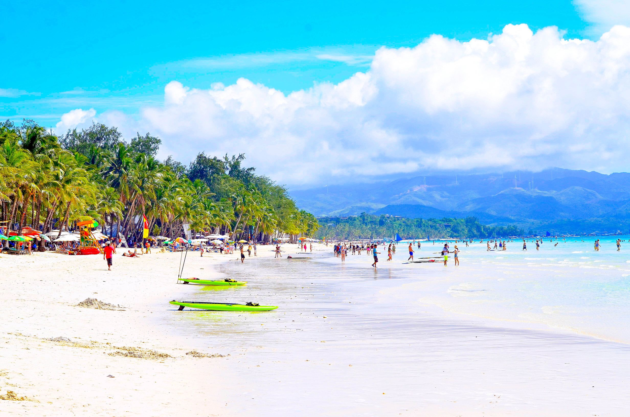 People on white sand beach with coconut palms and blue waters