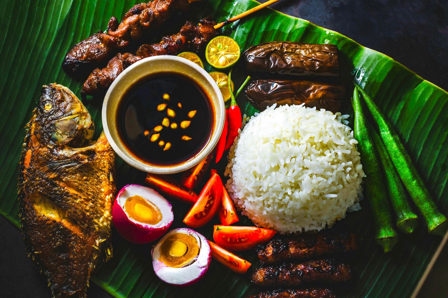 Rice, vegetables, eggs, and meats on banana leaves