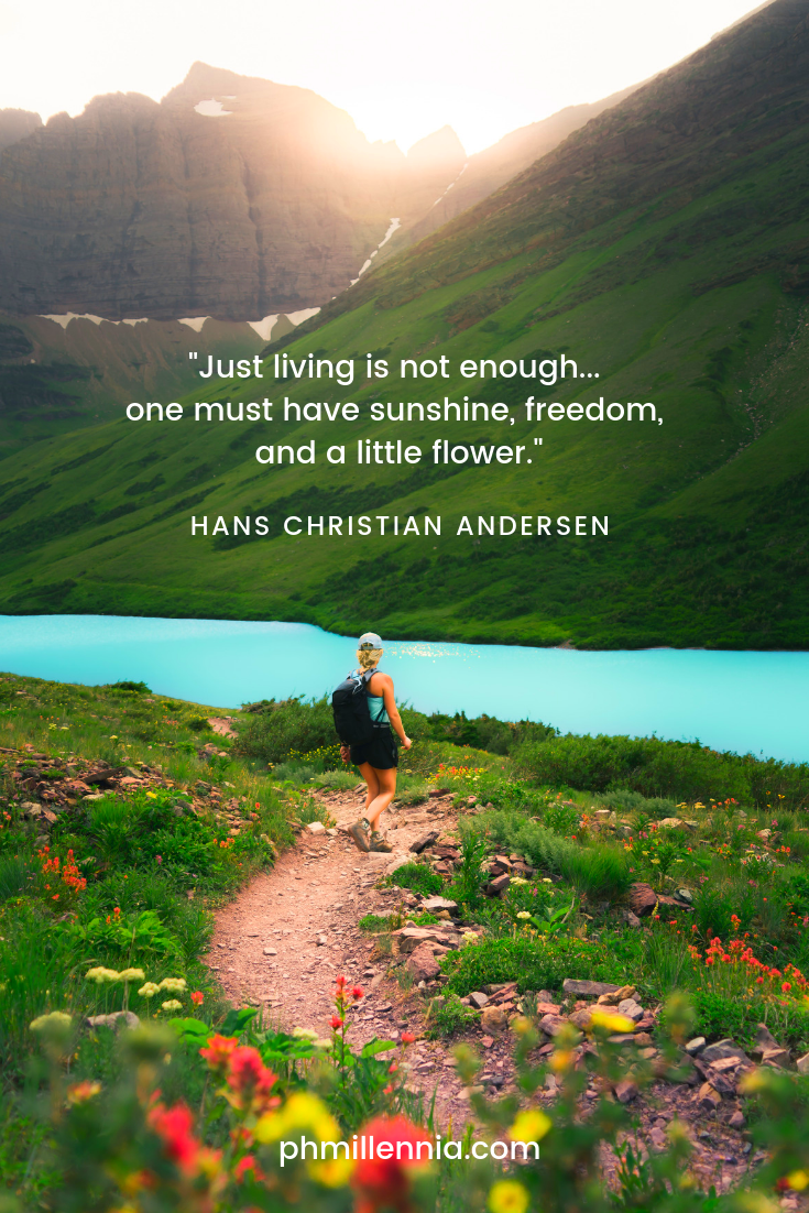 A quote on nature by Hans Christian Andersen on a background of a female backpacker walking along a road through a grassy field with flowers, leading to a river and mountains in the distance