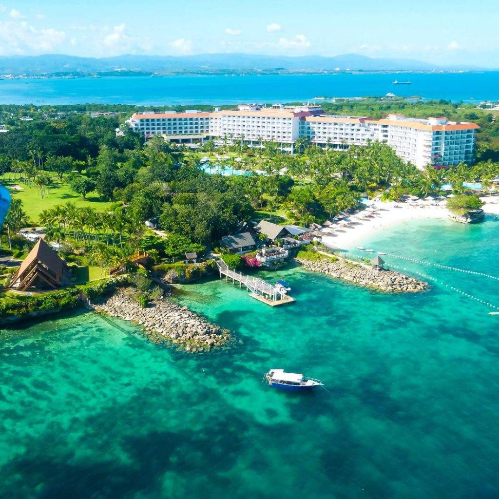 Luxury hotel with green lawns along a white sandy beach facing turquoise waters in Mactan Island, one of the most beautiful beach destinations in the Philippines