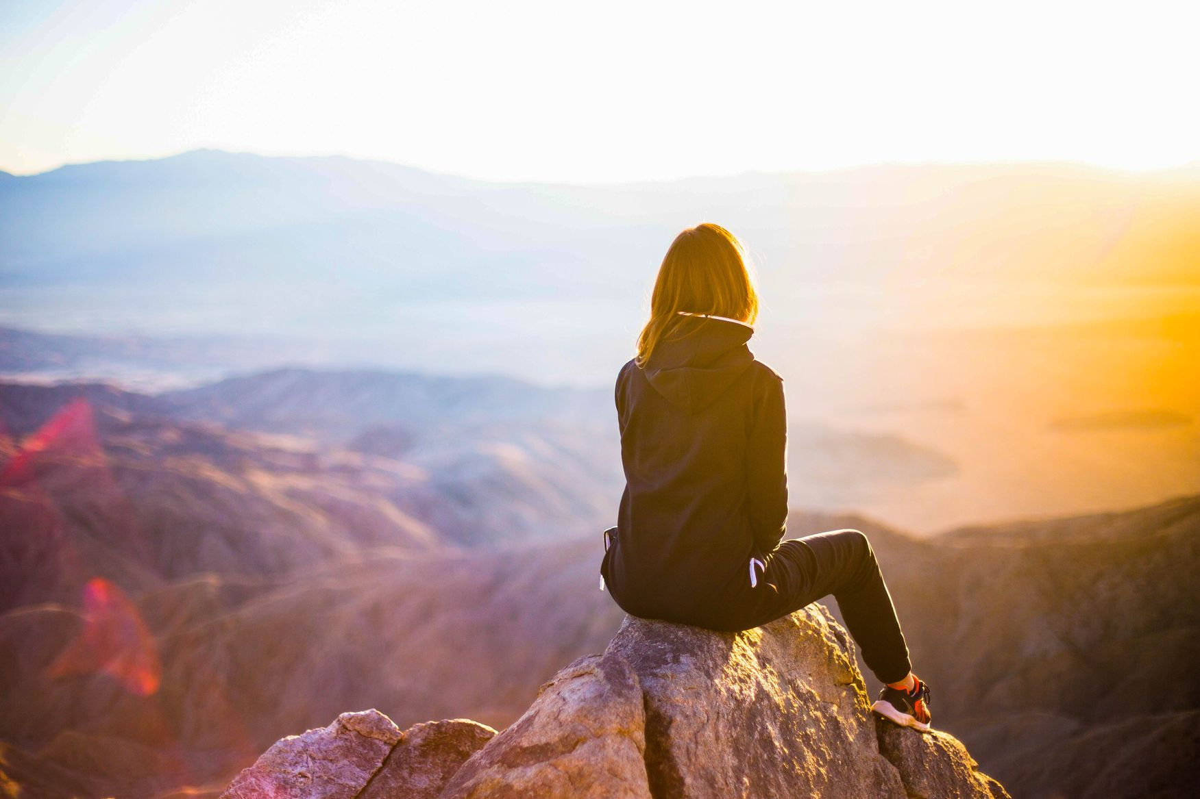 Woman sitting on a rock overlooking mountains
