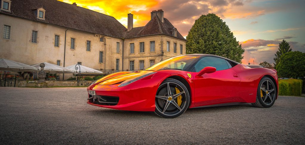 red sports car with a mansion in the background