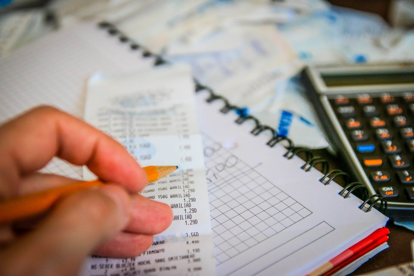 Hand holding a pencil over a receipt surrounded by a notebook, calculator, and other things, indicating that budgeting is one of the most effective ways to stop overspending