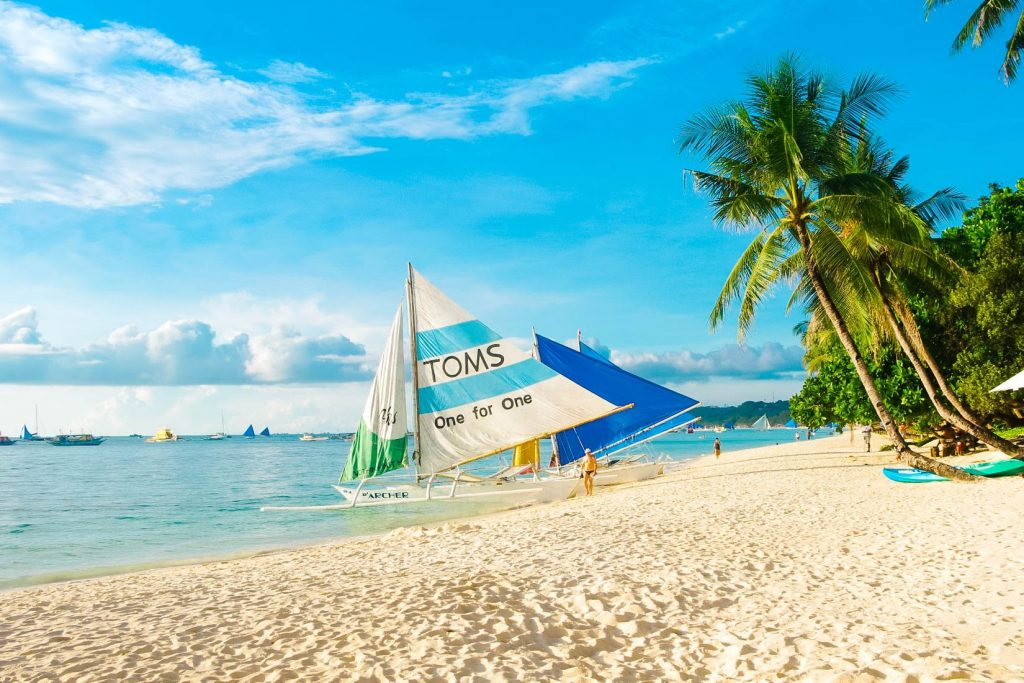 Coconut palms and moored sailboats on a white sandy beach in Boracay Island, one of the best places to visit in the Philippines