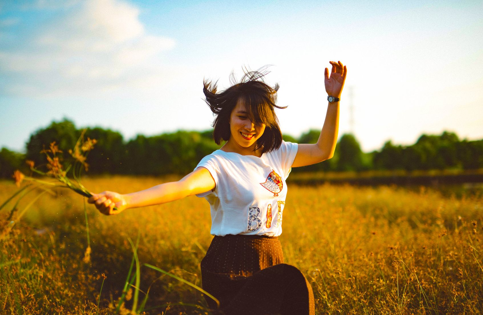 Woman jumping for joy in the middle of a grassy field (indicating that learning personal finance can help you become debt-free)