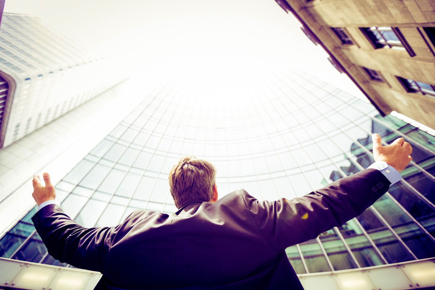 Man on a suit looking upwards with arms wide open, indicating that learning finance can help you fulfill your life goals