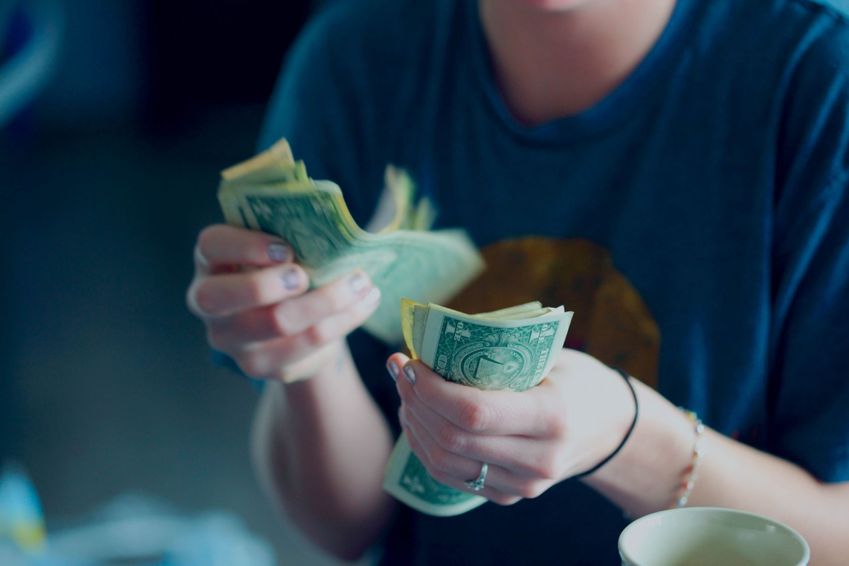 Woman's hands counting out multiple dollar bills