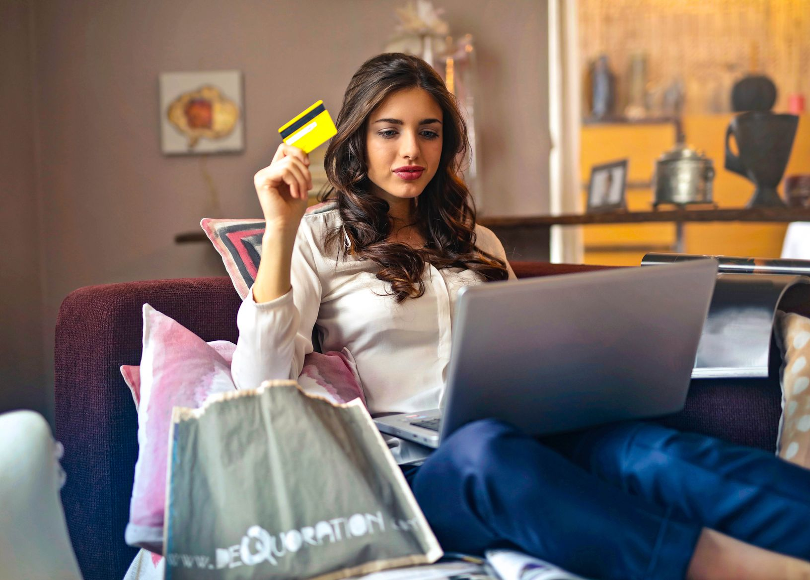 Woman holding a credit card with a laptop on her lap, indicating that responsible use of credit cards is one way to stop overspending