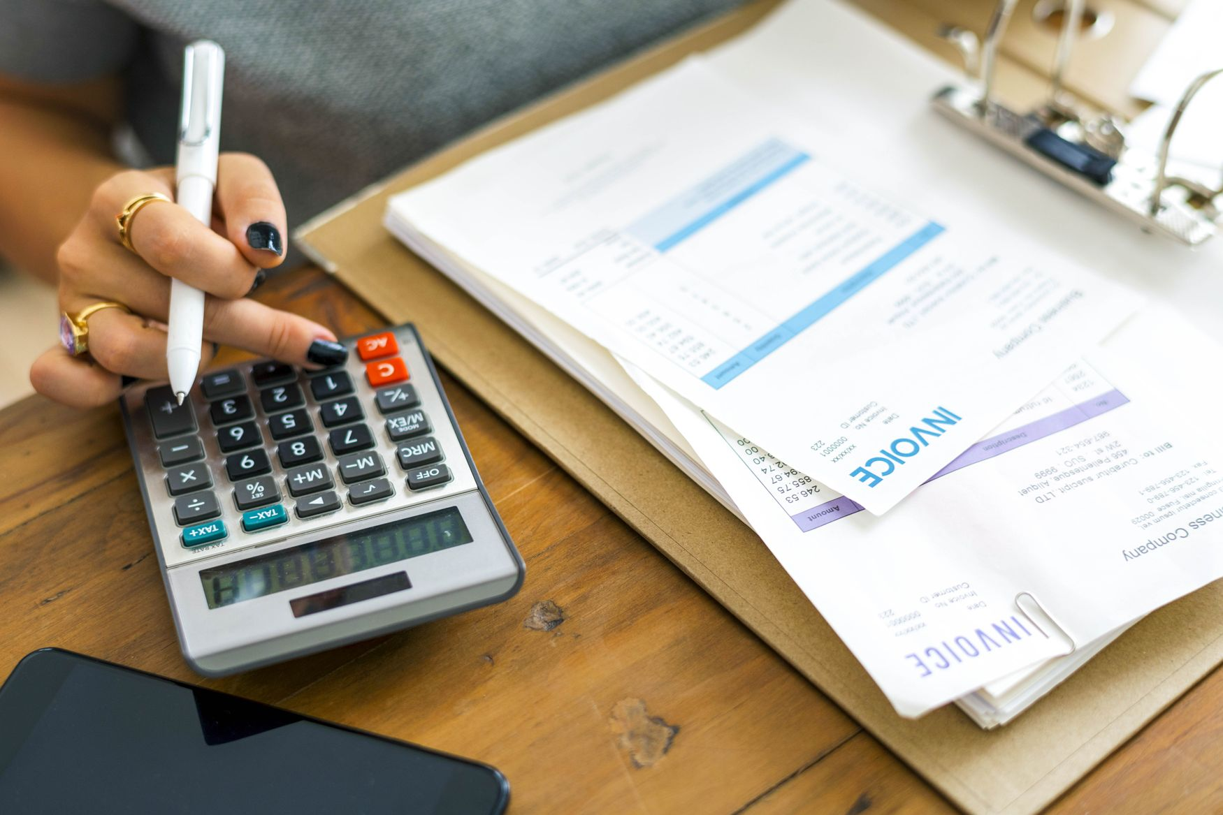 Woman's fingers on a calculator beside a stack of receipts