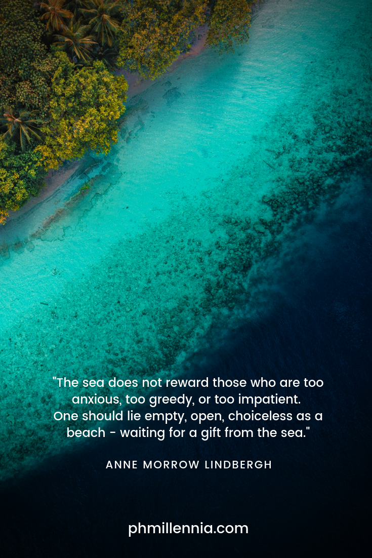 A quote on the sea by Anne Morrow Lindbergh with a background of an aerial (top) view of the sea and the shore filled with coconut palms and other trees
