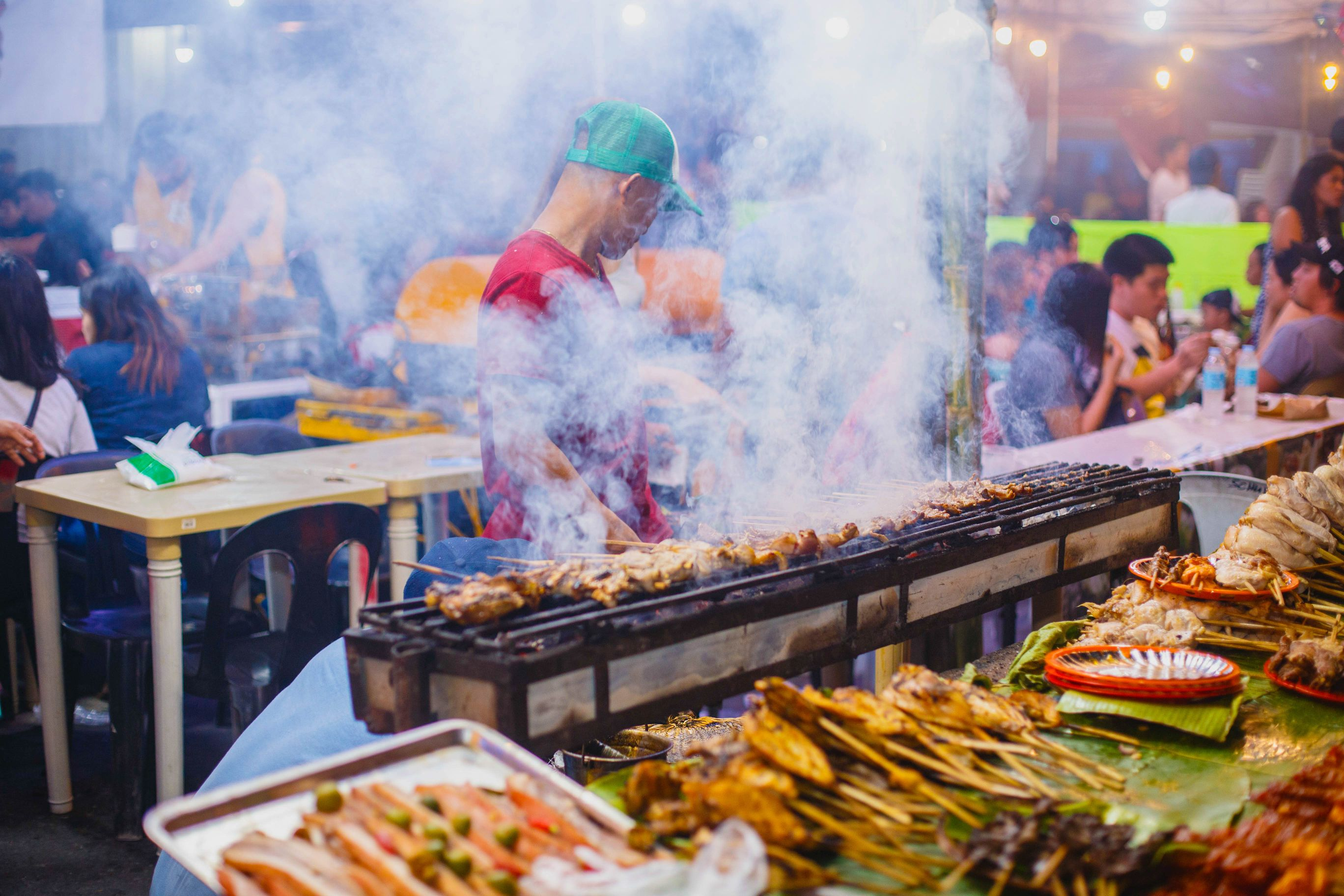 Man grilling skewered food a street food stall