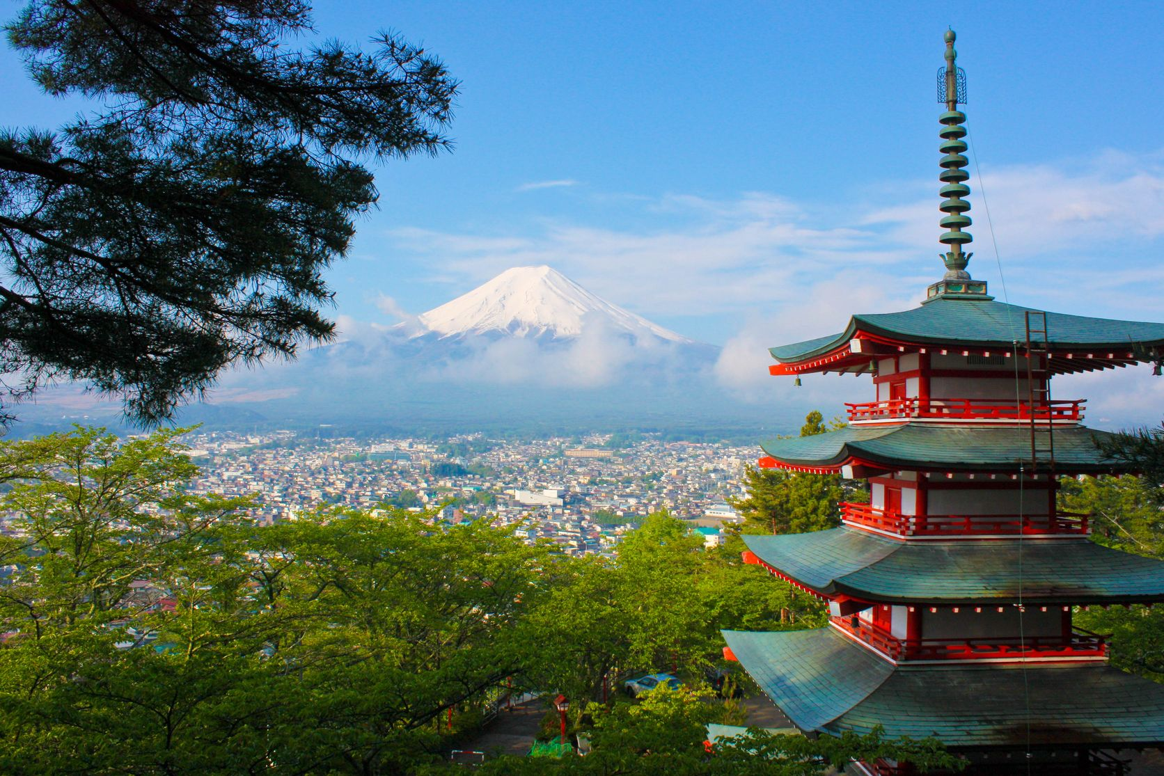 Japanese pagoda overlooking a city with snowy Mount Fuji in the background