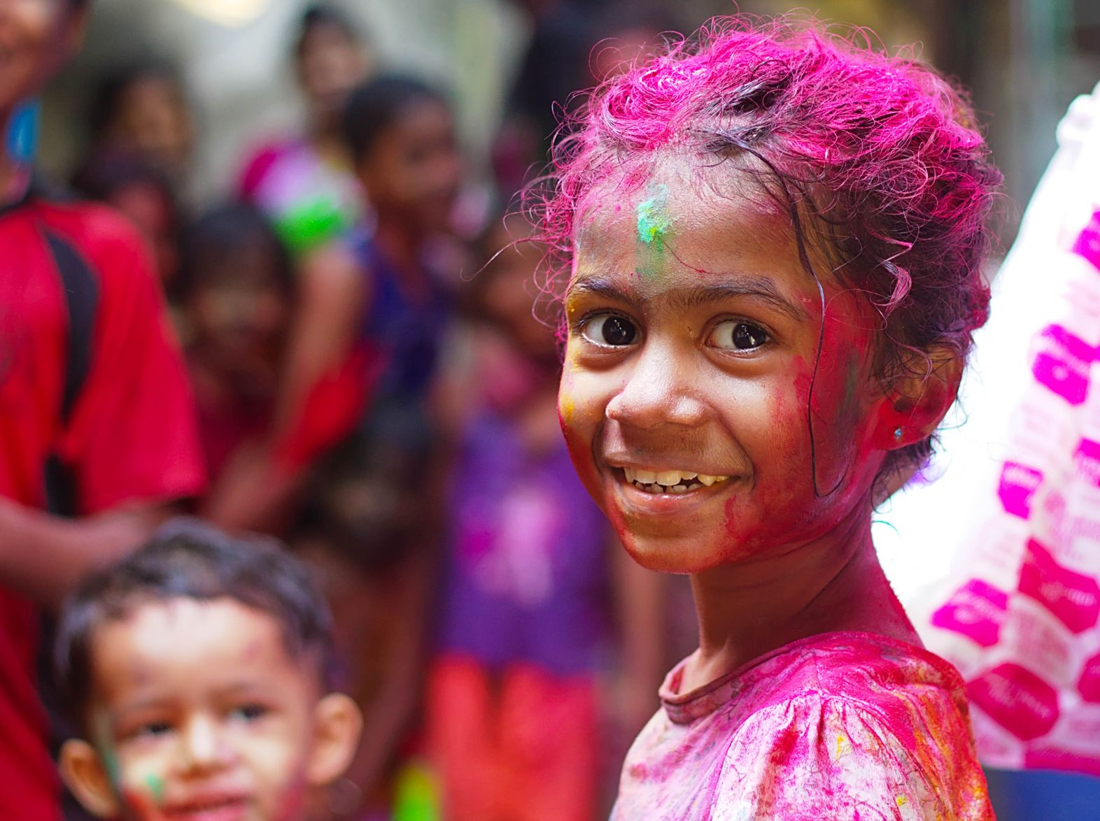 Female child with paint all over her face and hair smiling into the camera