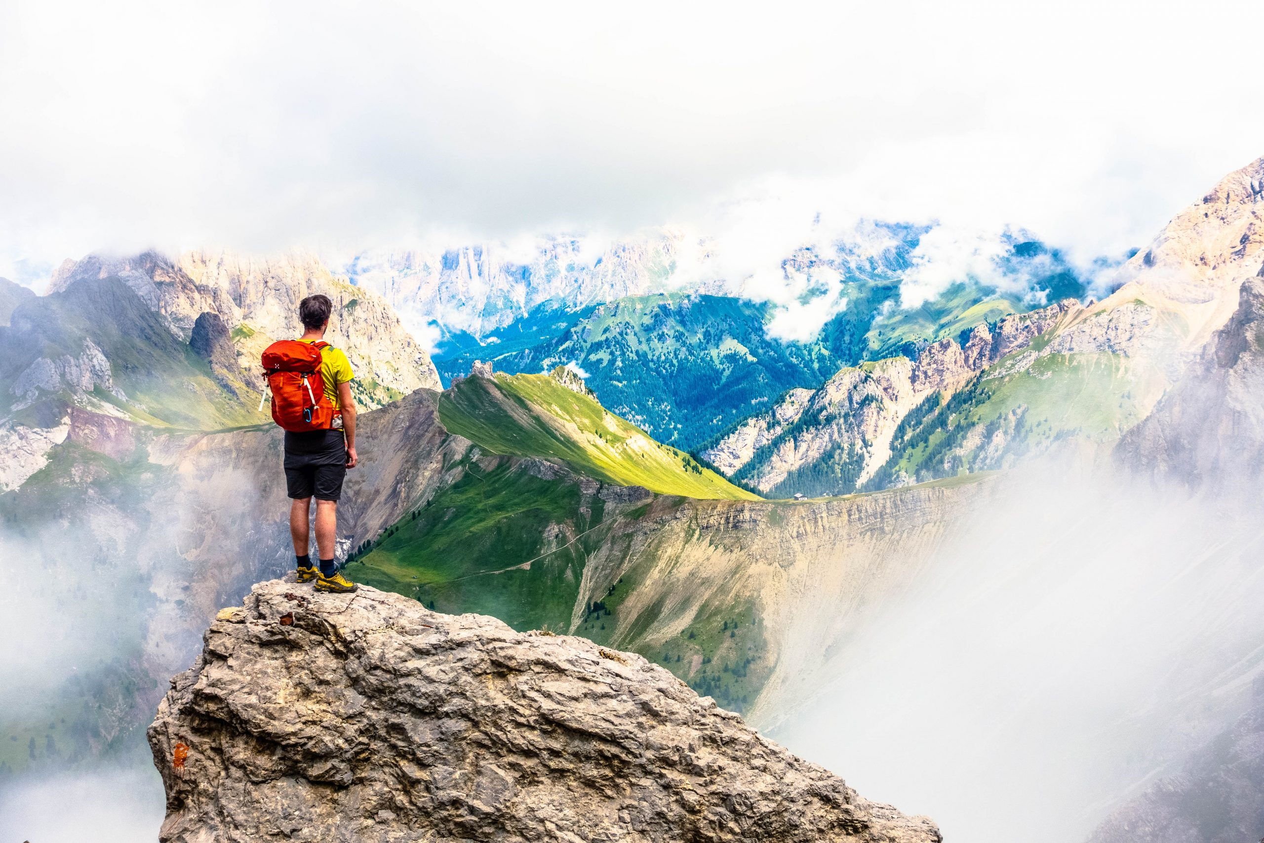 """An image of a man standing upon a rock overlooking green and blue mountains swathed with mist and fog - used as a featured image for the article entitled """"Why Travel? 9 Reasons Why You Need to Go Out and See the World"""" on phmillennia"""