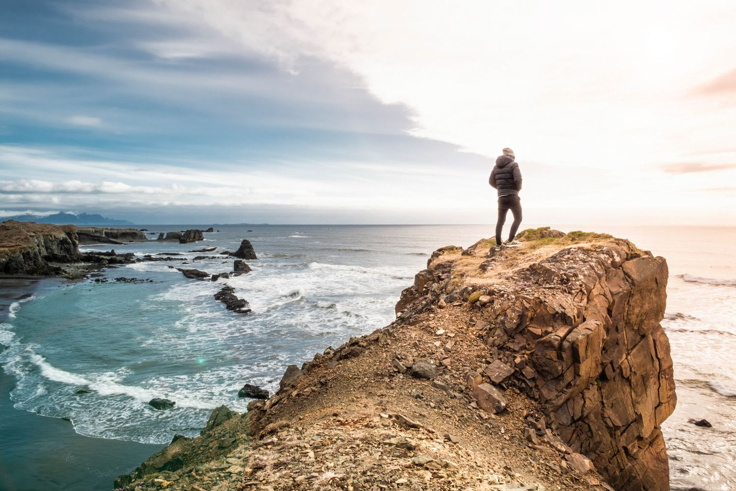 Man standing on a cliff towering above the sea