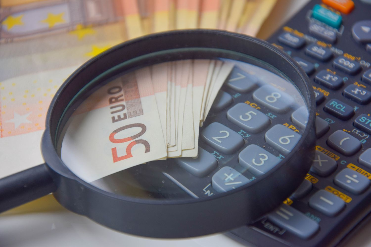 Money bills, calculator, and a magnifying glass to indicate personal finance management