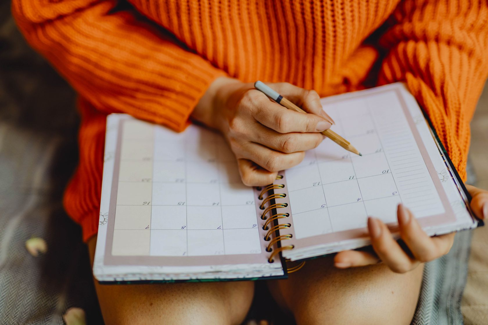 Woman writing a schedule on a planner with a pencil to become more productive