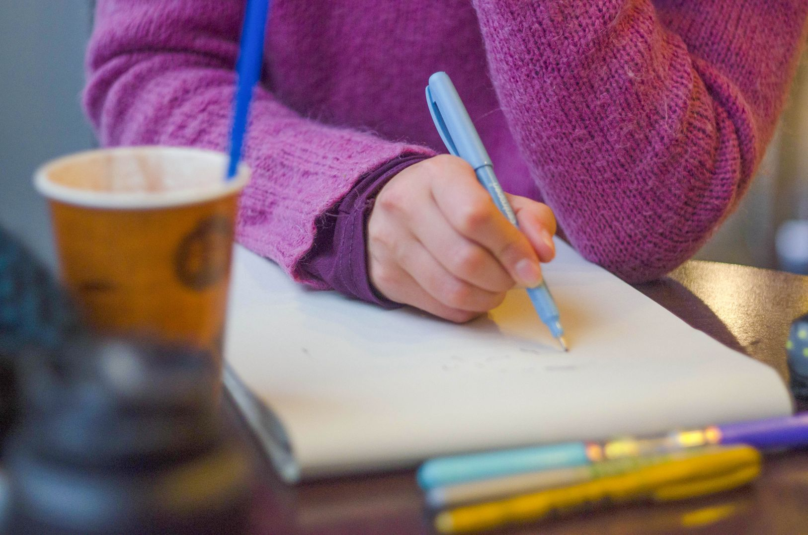 Woman in violet sweater writing on a notebook to indicate creating a to-do list to help her stop procrastinating