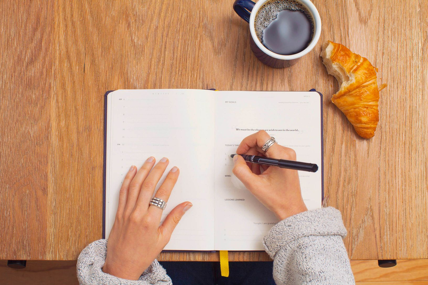 Overview of a pair of woman's hands writing with pen on a notebook laid open on a wooden desk, with a mug of coffee and a bitten croissant nearby