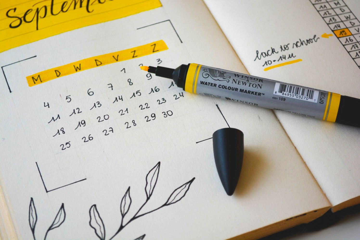A marker and its cap set atop an open planner with a calendar on one page