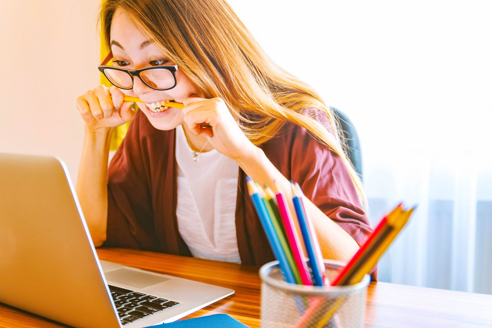 A bespectacled woman staring at her laptop while holding a pencil between her teeth,