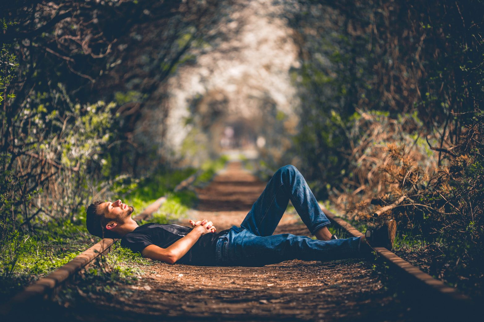 A man lying on railroad tracks that run through forest to indicate that he is procrastinating