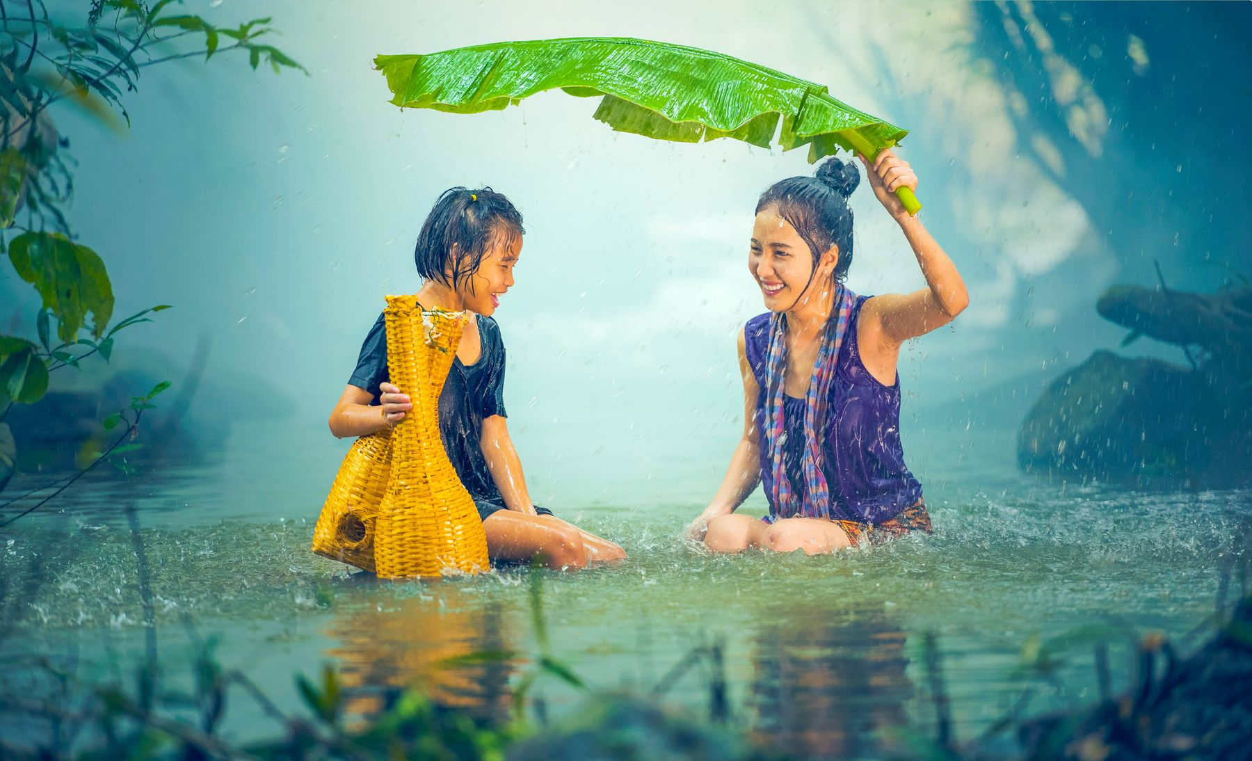 A happy mother holding a banana leaf over her and her child's head to cover them against the rain
