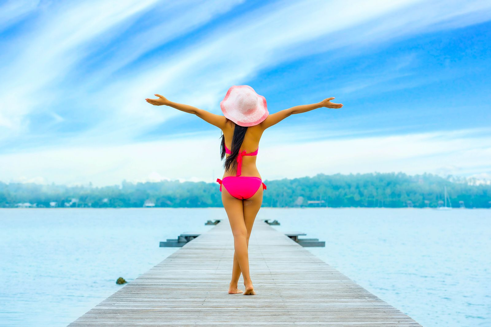 Woman on a bikini standing on a pier with arms outstretched above her head, her back turned to the camera