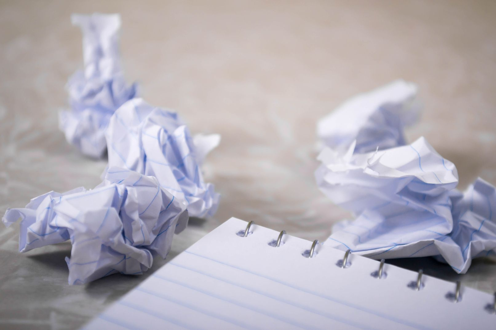 Crumpled pieces of paper next to a notebook