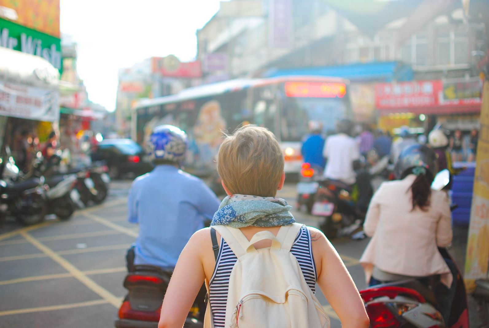Traveling female backpacker with her back to the camera, facing a busy street on a foreign country, indicating that travel promotes creativity, a career skills you learn from traveling