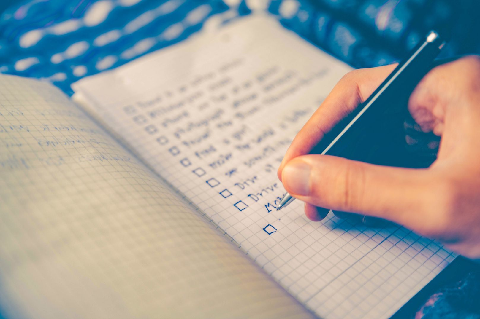 Hand holding a pen, writing a to-do list on a notebook, indicating that knowing how to prioritize tasks is crucial to effective time management