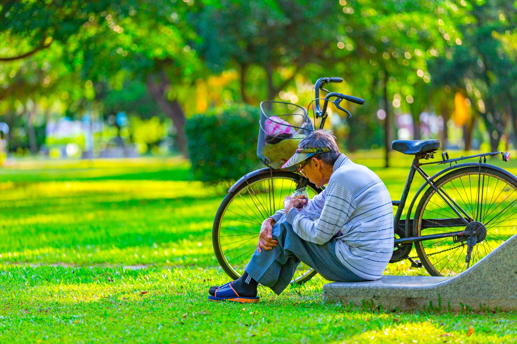 An old man with his bicycle, sitting on a concrete step out in a green park with green trees
