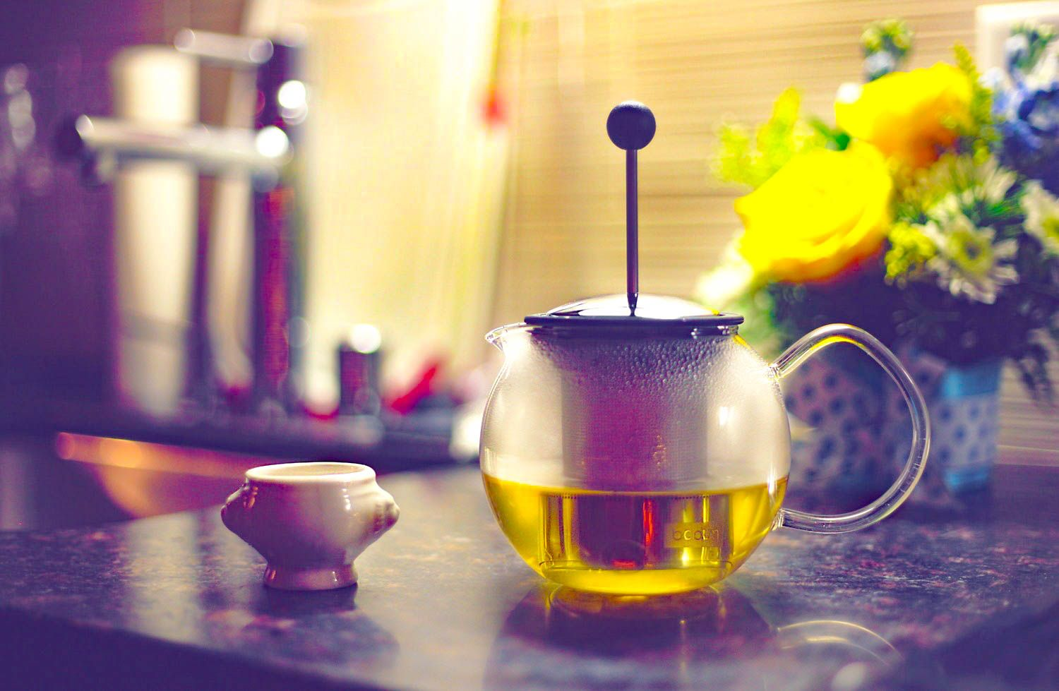 A glass teapot and a teacup on a wooden desk