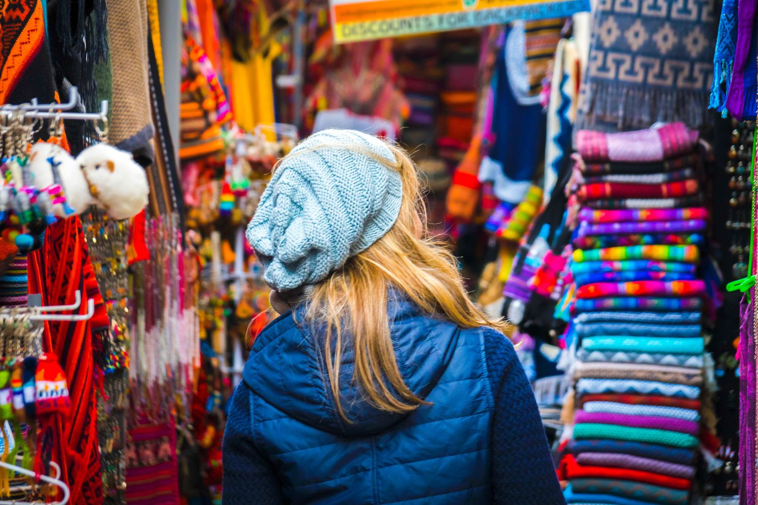 Female backpacker with her back to the camera walking through a busy marketplace, indicating that budgeting is a career skills you learn from traveling