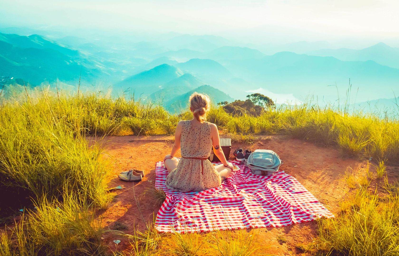 Woman sitting on a picnic blanket spread out on top of a grassy clearing overlooking a misty mountain range